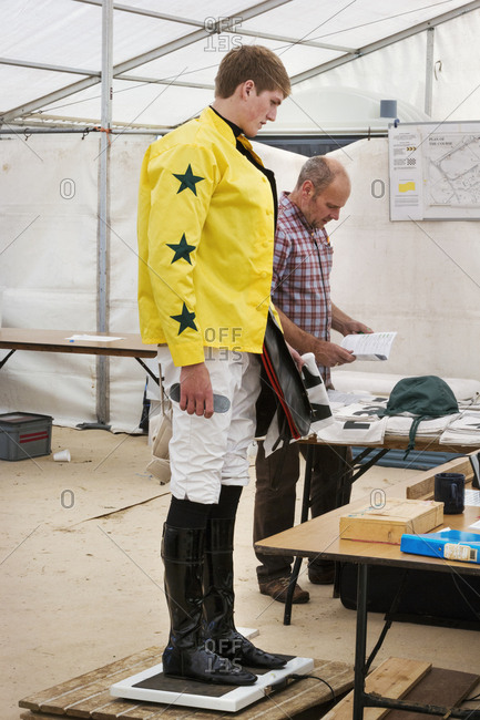 Jockey in a yellow shirt standing on weighing scale, being weighed before a horse race.