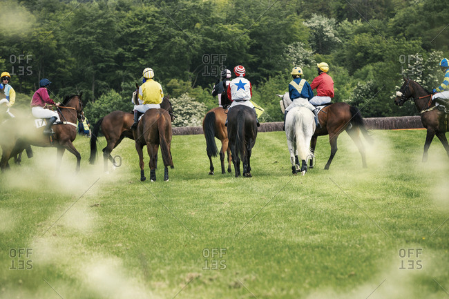 Group of riders on racehorses on a racecourse in a line.