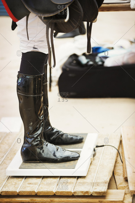 Rider wearing shiny black riding boots at the weigh in  on weighing scale, holding a saddle, before or after a race.