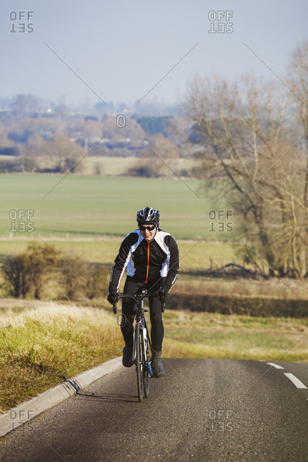 A man pedaling out of the saddle on a road bike, climbing up a hill. Front view.