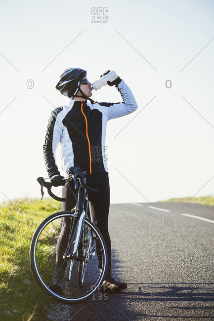 A cyclist by the side of a road, having a break and drinking from his water bottle.