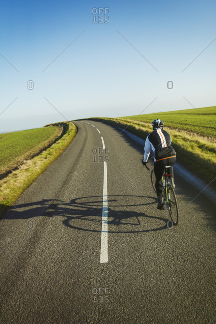 A cyclist pedaling along a country road, rear view.