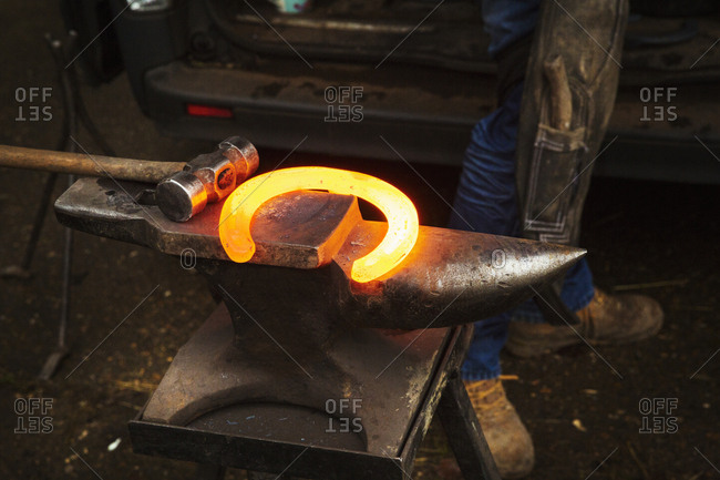 A hammer and anvil, and a red glowing heated metal horseshoe.