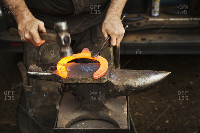 A farrier using tongs and hammer to hold and shape a red glowing heated metal horseshoe to be fitted.