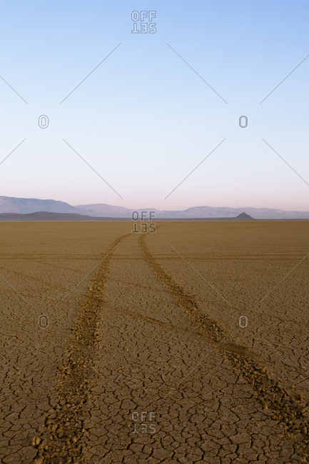 Tire tracks in a desert landscape with mountains in the distance.