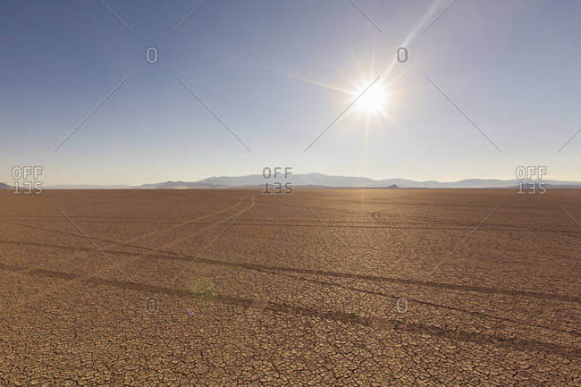Tire tracks in a desert landscape with mountains in the distance. against a blue sky.
