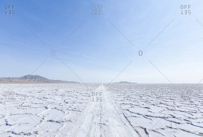 Cracked earth in a desert landscape against a blue sky with mountains in the distance.