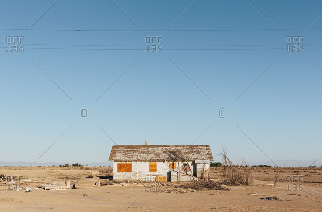 A boarded-up wooden house in an arid landscape against a blue sky.