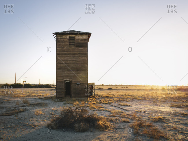 A wooden tower standing in a flat landscape of scrubland.