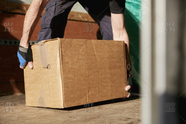 Removals business. A man lifting a cardboard box off the floor.