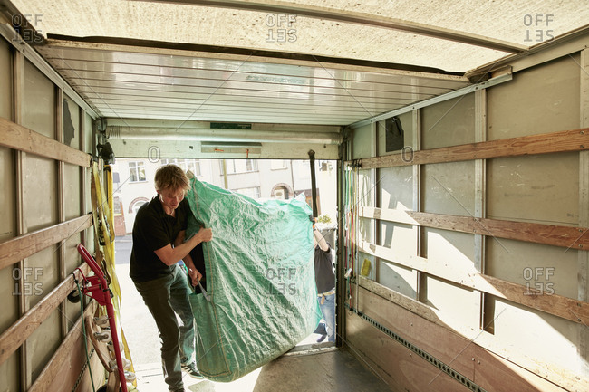 Removals business. A man lifting an item of furniture covered in green plastic into a removals van.