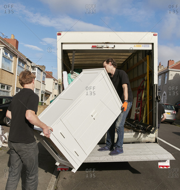 Removals business. Two men lifting a wardrobe onto the removals van.