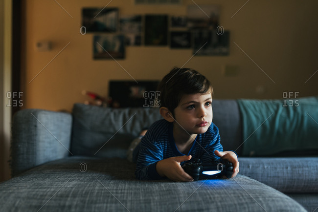 Young boy focuses on playing a video game