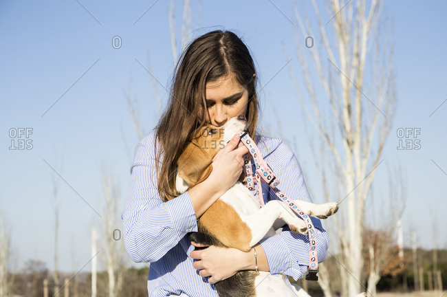 Woman kissing her dog in a park