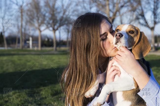 Beautiful woman kissing pet beagle in park