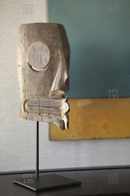 Hand-carved tribal mask on stand