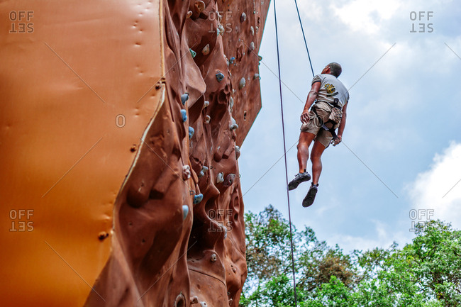 May 30, 2013 - Nainital, Uttarakhand, India: Climber rappelling from rock wall