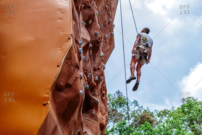 May 30, 2013 - Nainital, Uttarakhand, India: Climber rappelling from rock wall