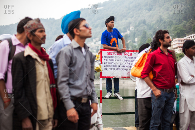 June 9, 2013 - Nainital, Uttarakhand, India: Sikh man standing on railing at lake among crowd of men