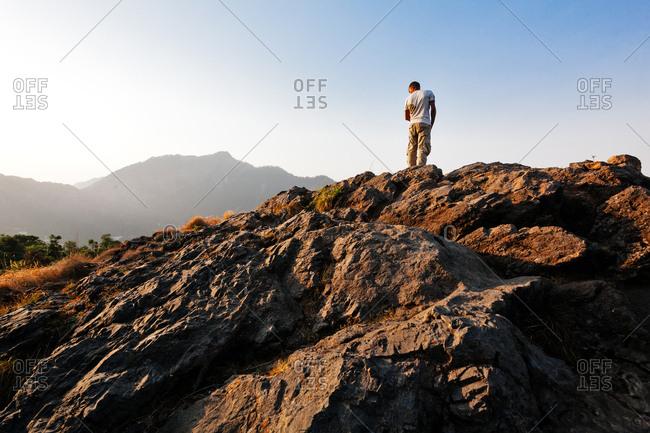May 29, 2013 - Nainital, Uttarakhand, India: Hiker on rocks at sunset