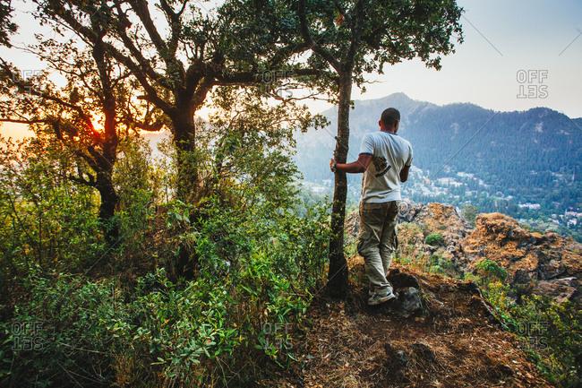 May 29, 2013 - Nainital, Uttarakhand, India: Hiker overlooking valley at dusk