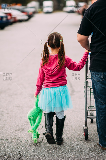Girl holds her stuffed animal and father's hand