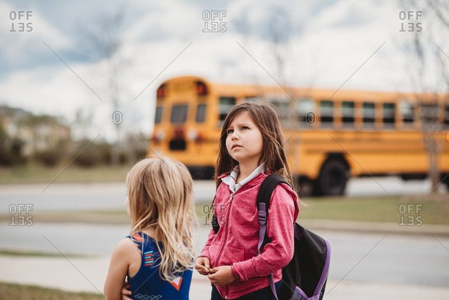 Two young girls waiting at bus stop