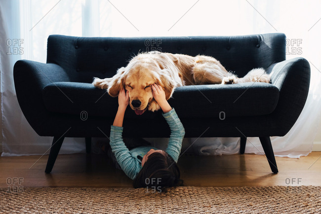 Girl under sofa playing with dog