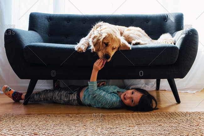 Girl under couch playing with dog
