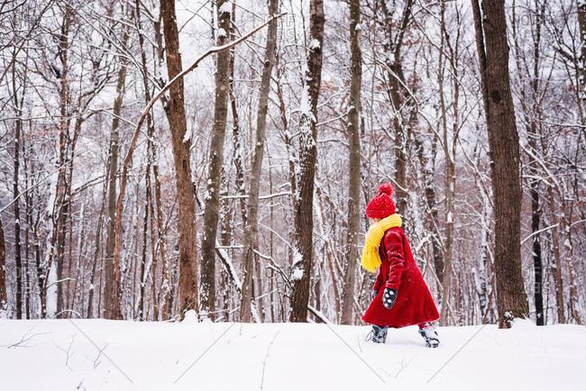 Girl strolling alone in snowy woods
