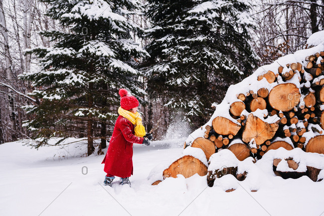 Girl throwing snow at wood pile