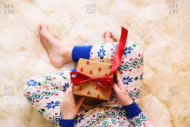 Child in winter pajamas holding gift