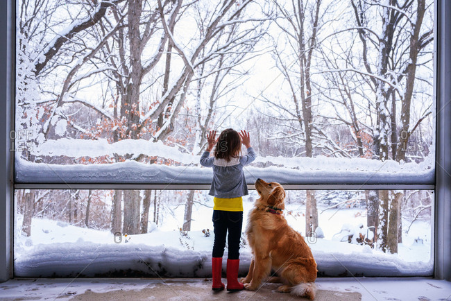 Young girl and dog looking at snow outside