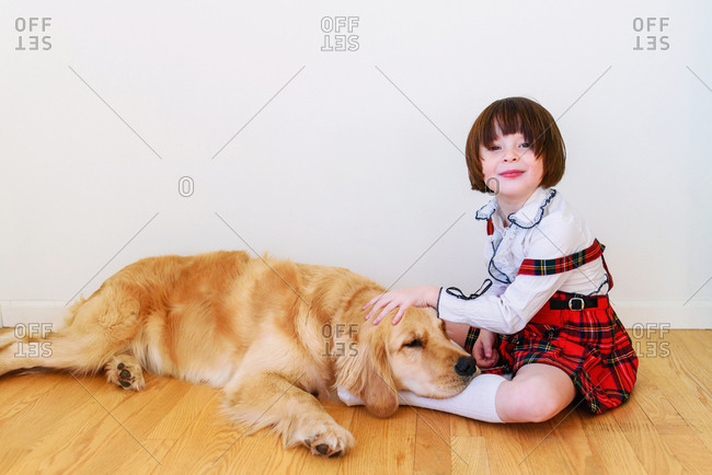 Dog resting by girl on floor