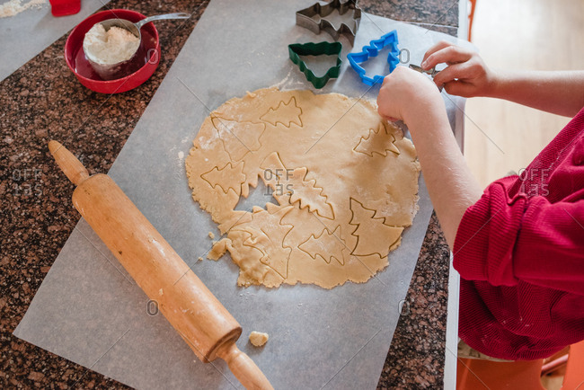 Child rolling out Christmas cookies