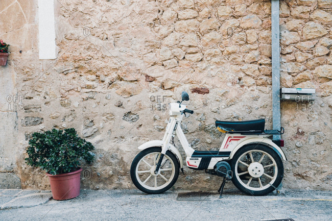 Mallorca, Spain  - January 11, 2017: Scooter outside a stone building