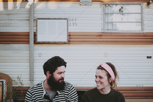 A couple sitting outside an RV