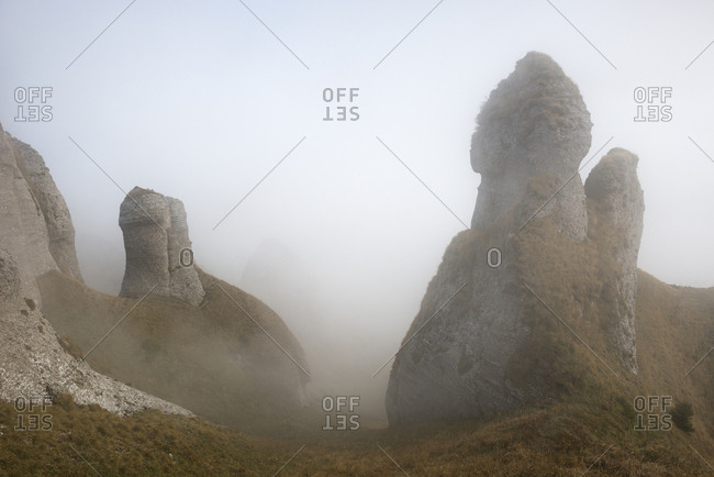 Fog shrouds conglomerate rock formations in the Ciucas Mountains.