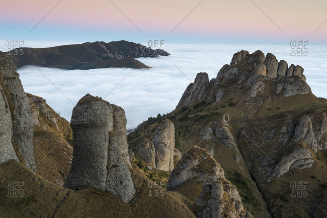 Thick cloud cover rolls to the base of conglomerate rock formations in the Ciucas mountains.