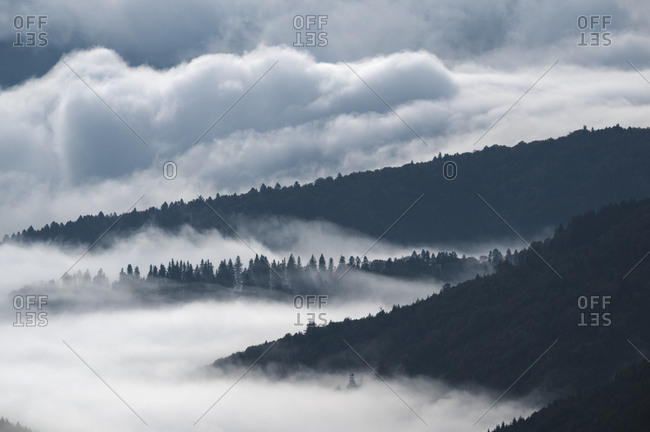 Mist covers the valleys and slopes of the Piatra Mare Mountains in autumn.