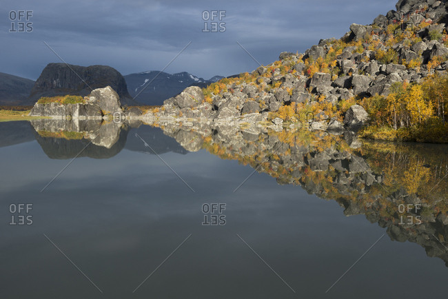 A rocky shoreline is reflected in a lake's calm waters in autumn.