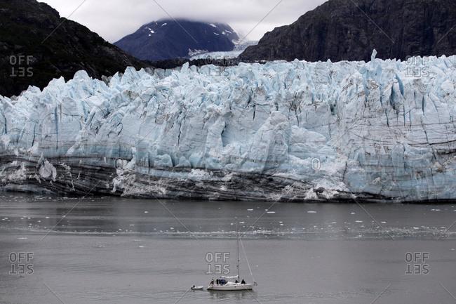A boat sails in front of Margerie Glacier in Glacier Bay National Park, Alaska.