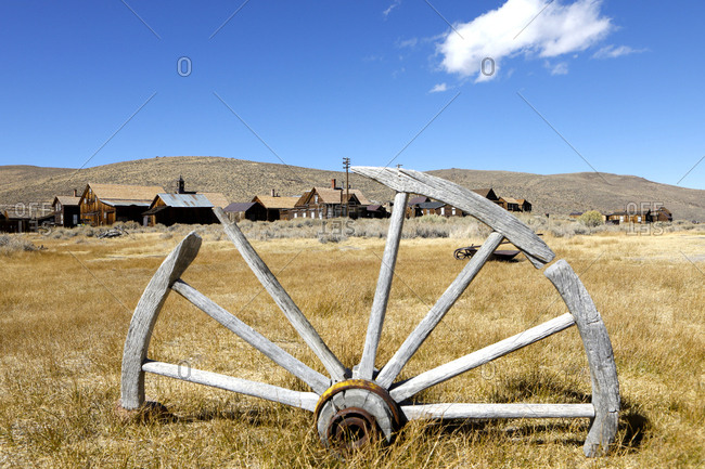 Close up of old wooden wheel with abandoned houses in the background at Bodie Ghost Town.
