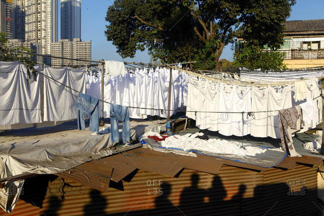Shadows of people walking by laundry hanging to dry at the  Dhobi Ghats.
