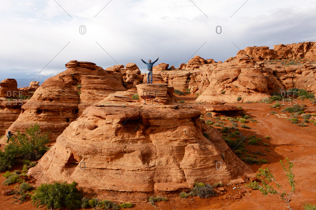 A man standing on top of a rock formation in Saint George, Utah, USA.