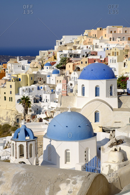 Greece - September 16, 2016: Blue domes of Greek Orthodox churches combine with colorful pastel homes in Santorini, Greece.