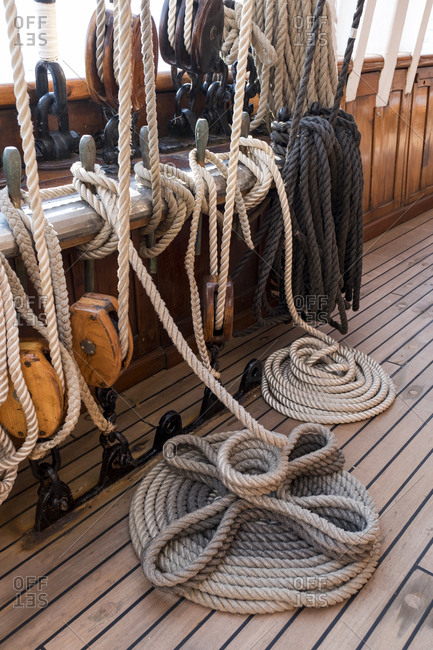 Rope lines on a tall masted ship are secured in an orderly and occasionally decorative fashion.