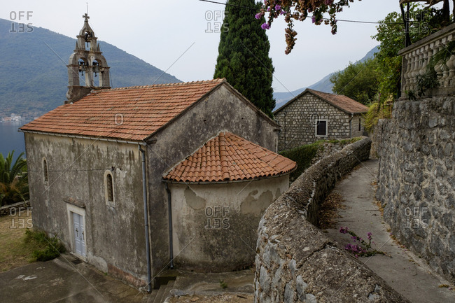 The narrow side streets in the town of Perast lead to pathway and churches with terracotta tile roofs.