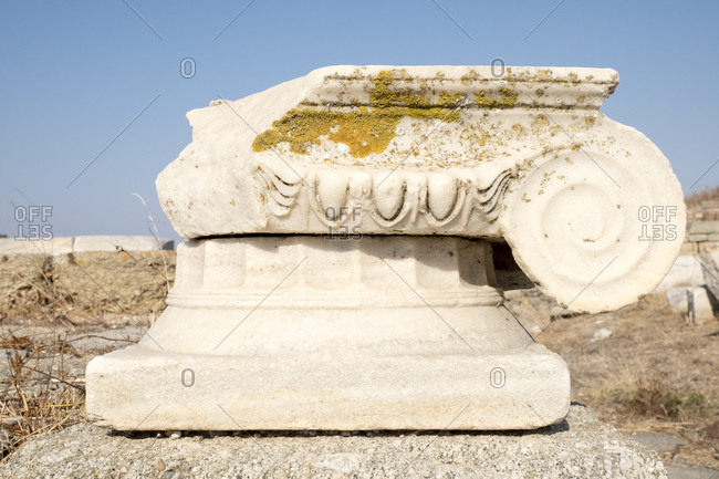 A detail of the top of an Ionic marble column covered in lichen at the Delos archaeological ruins in Greece.