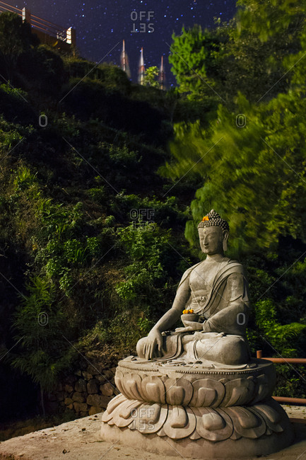 A Buddha statue sitting in Lotus Position at night in Nagarkot, Nepal.
